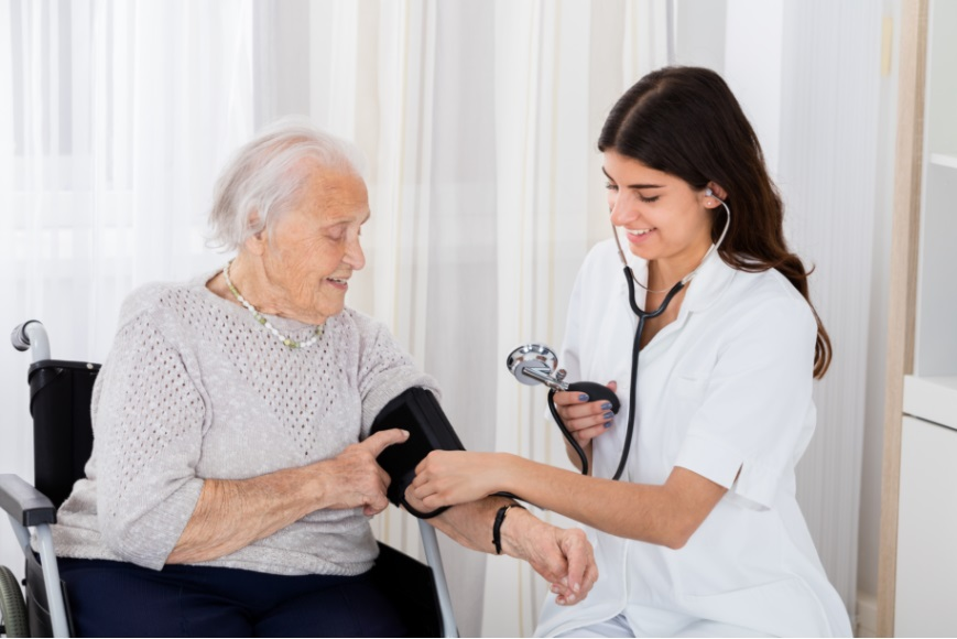 Happy Female Doctor Measuring Senior Patient Blood Pressure With Stethoscope In Hospital